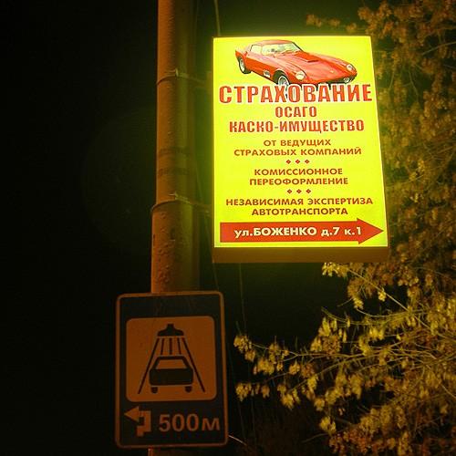 Ночной вид рекламного указателя на опоре уличного освещения