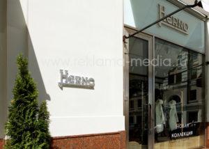 Металлические вывески на стекле над входом в бутик одежды и на фасадной колонне