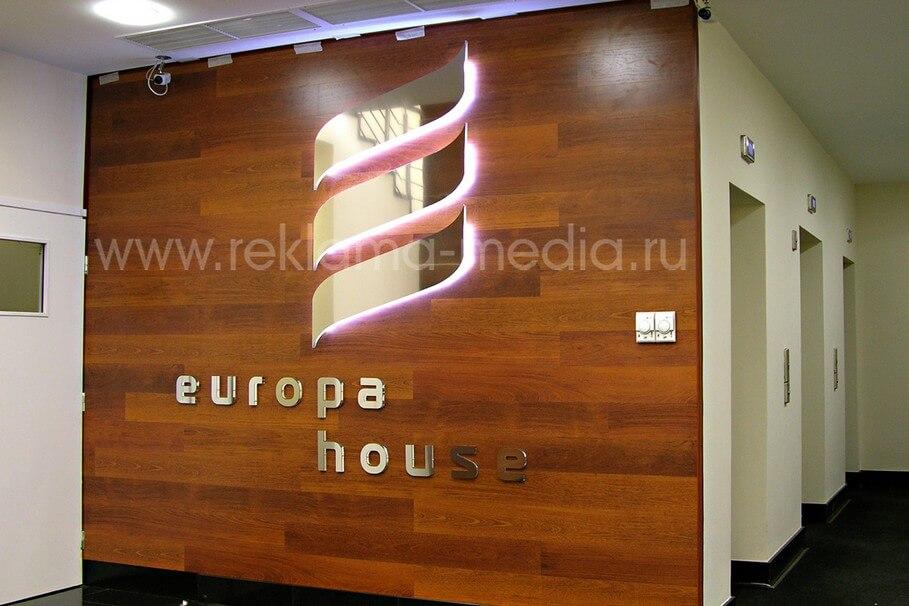 Интерьерная световая вывеска в холле бизнес центра Объемные буквы и знак из сэндвича толстостенного акрила и глянцевой стали