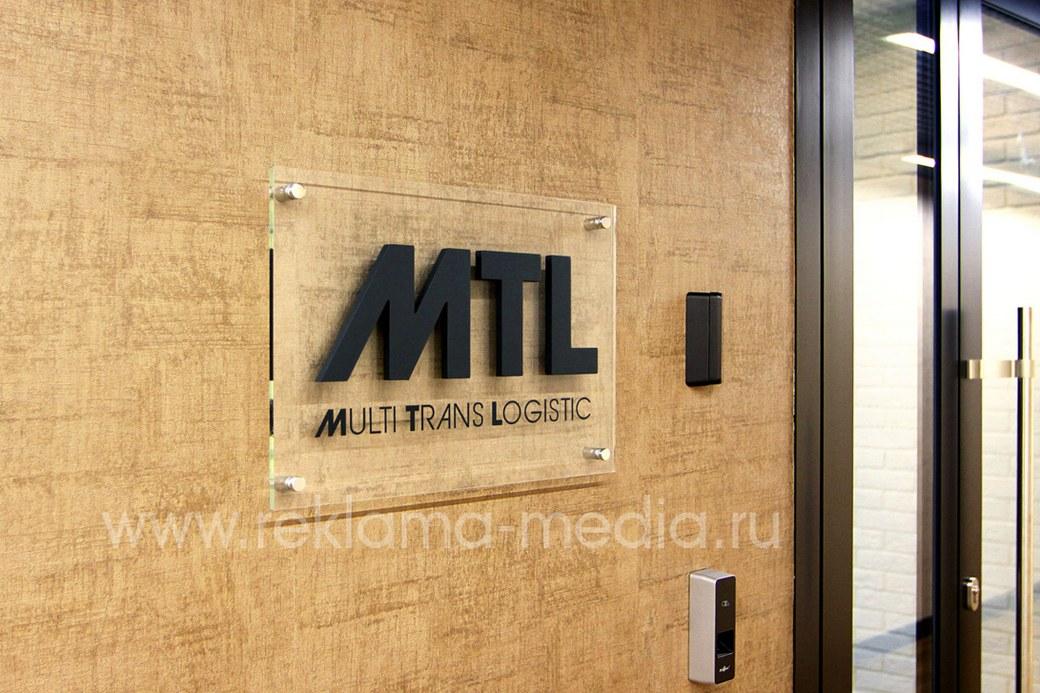 Акриловая табличка на фоне входной двери в организацию