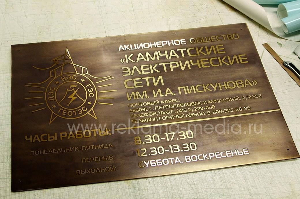 Большая латунная табличка с телефонами и часами работы организации